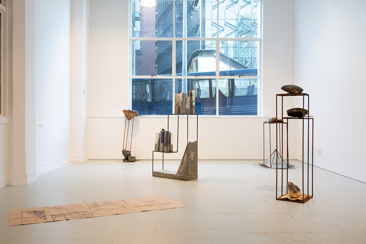 Installation view, map on floor, metal plinths displaying objects