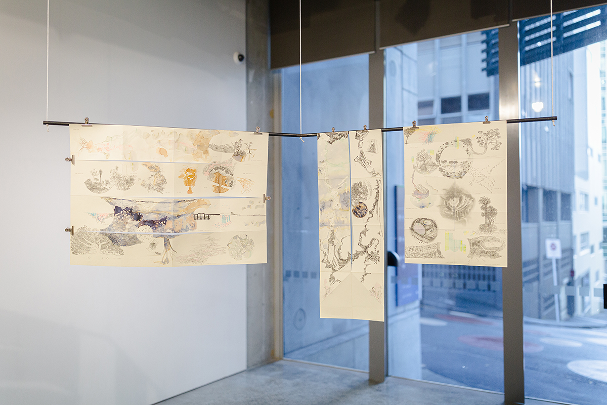 Three drawings hung from metal rod